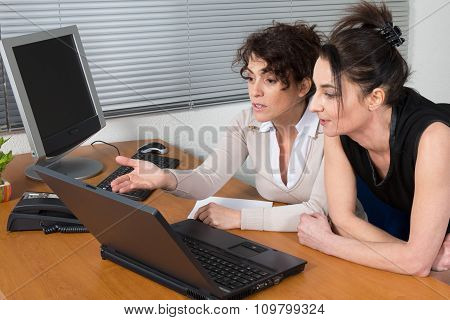 Two Women Working Together In A Bright Office
