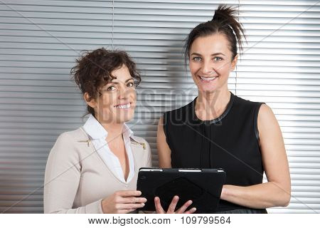 Two Business Women With Computer Tablet In The Office.