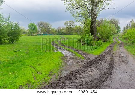Landscape with dirty road in rural Ukrainian area at spring season . It's overcast and rainy weather