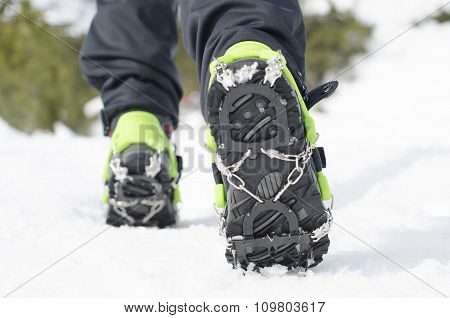Hiking boots with equipment for ice. Snow background. Natural. Technology for climbing