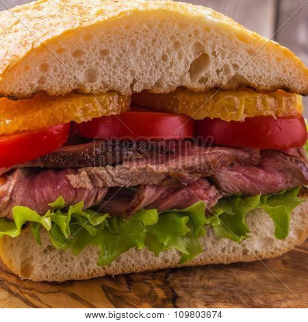 Juicy Steak Sandwich With Vegetables And Slices Of Orange.