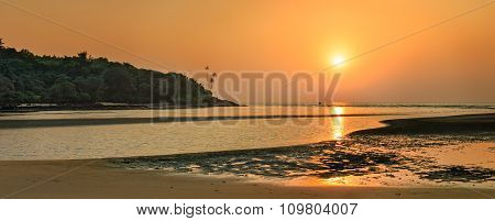 Tropical beach in ebb time on sunset background Mobor Beach South Goa India