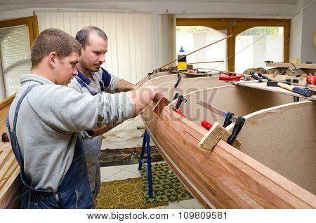 Young Carpenters Assembling New Canoe Of Their Own Design