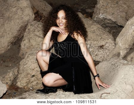 Woman In Black Dress Kneeling On Concrete Ledge