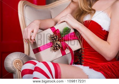 Beautiful girl wearing santa claus clothes with christmas gift in hand. Christmas concept
