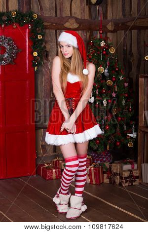 Beautiful sexy girl wearing santa claus clothes at new year interior. Young female posing in christm