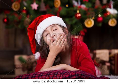 Portrait of cute girl in Santa hat fell asleep under Christmas tree