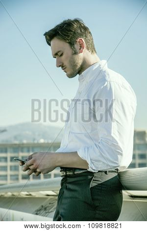 Handsome trendy man using cell phone to type text, outdoor