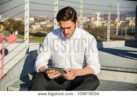Handsome trendy man looking down at a tablet computer, outdoor