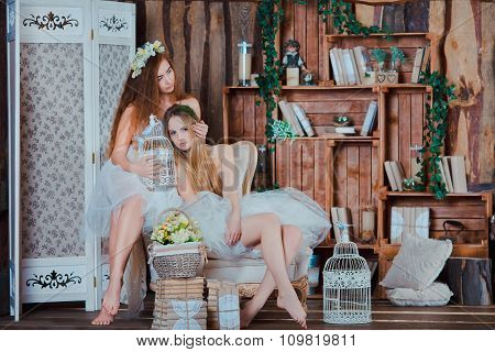 Two beautiful sensual girls with perfect slim legs sitting in vintage interior