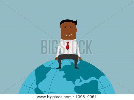 Happy businessman sitting on the earth globe
