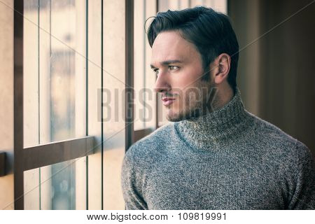 Handsome serious man standing inside modern building