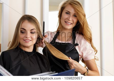 Beautiful Blonde Female Hairdresser Holding Lock Of Hair In Hands And Picking Proper Hairdo