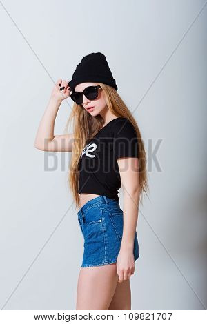 Fashion portrait of beautiful sexy young girl in jeans shorts and sun glasses on white background