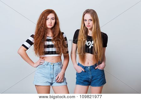 Two beautiful sexy young girls in jeans shorts on white background