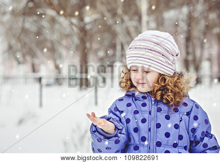 Little Girl Held Out A Hand In Which Falling Snowflakes. Winter Portrait.