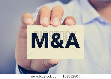 M & A Letters (or Merger And Acquisition) On The Card Held By A Man Hand