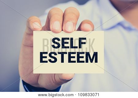 SELF ESTEEM message on the card shown by a man vintage tone