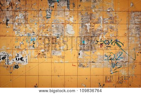 Yellow tiled wall with remains of ripped paper from advertising posters