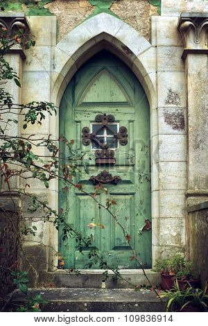 Old gothic door in romantic style with peeling green paint
