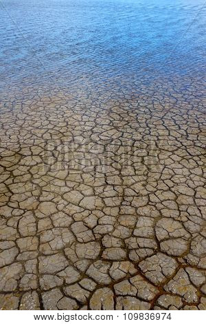 Background of cracked dry land covered with a thin layer of water