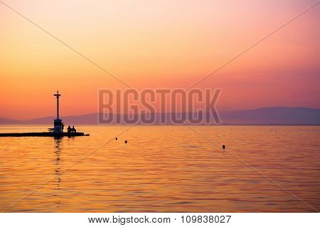 Sunset over a port and silhouette of fishermen