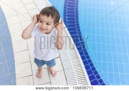 3 years old boy on resort pool enjoying