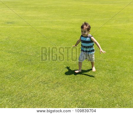 Little kid running on green meadow