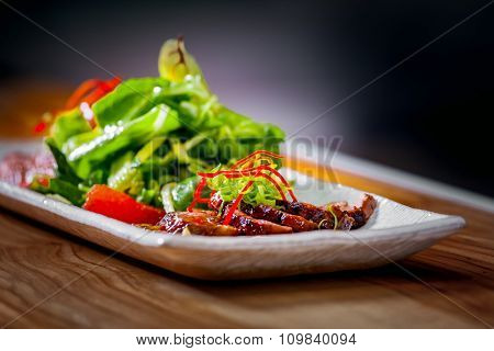 Delicious appetizer with herbs and meat on white plate close up