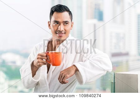 Asian man in morning front of city skyline drinking coffee