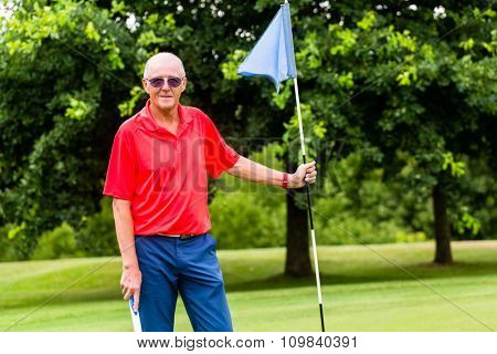 Senior man playing golf on course holding flag