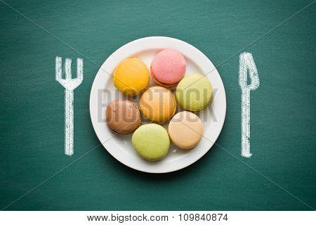 sweet french macarons and drawn cutlery on chalkboard