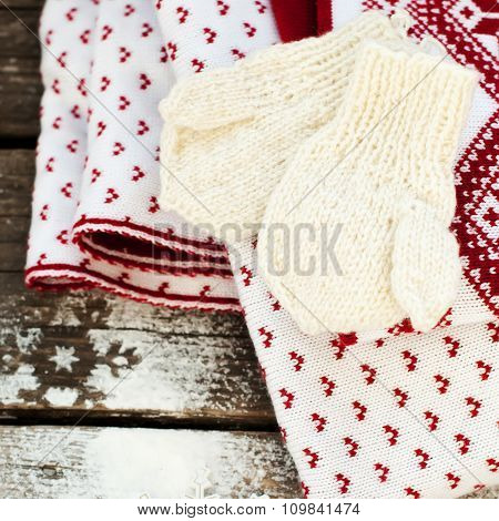 Mittens, Snowflakes And Plaid On Wooden Background