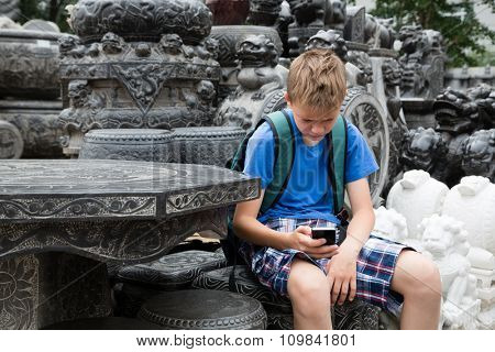 Caucasian boy backpacker talking on mobile phone on the famous Panjiayuan Antique Market, Beijing