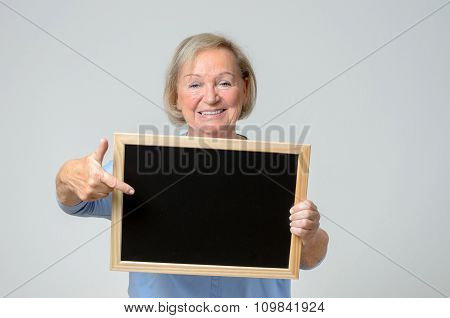 Enthusiastic Senior Woman Pointing To A Blackboard