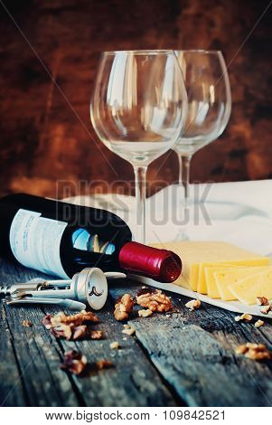Still Life With Red Wine, Glasses, Walnuts, Cheese And Opener On Wooden Table