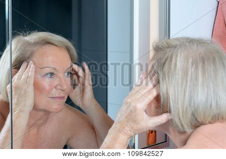 Senior Lady Checking Her Skin In The Mirror