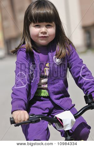 Cute Little Girl Driving Bicyle At Sunny Day