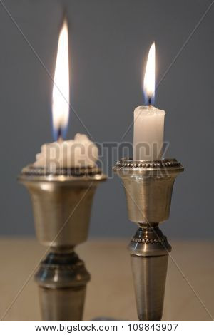 Two candlesticks with burning candles on dark background