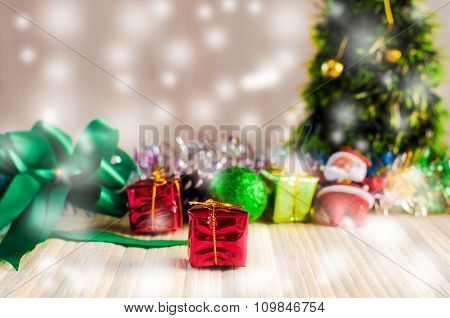 Santa Claus Doll Against A Christmas Tree With Gift Box On Wood Background And Snow White Drop