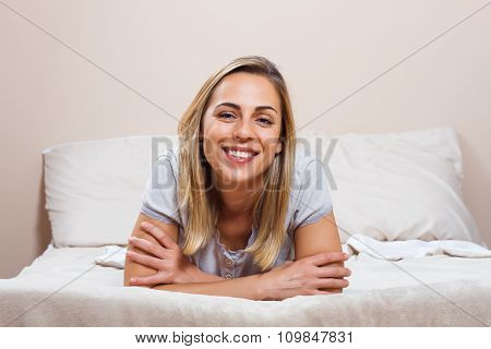 Happy woman lying on bed