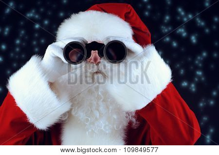 Portrait of Santa Claus looking through the binoculars over black background. Christmas time.