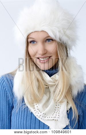 Portrait of attractive young blonde woman in white fur hat, smiling, looking away.
