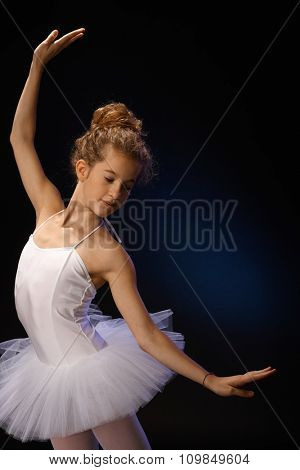 Young ballerina exercising over black background.