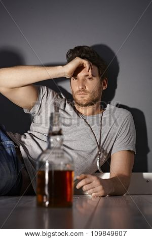 Depressed young man drinking whiskey.