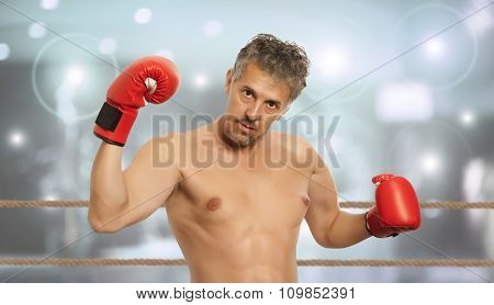 Muscular boxer in red boxing gloves