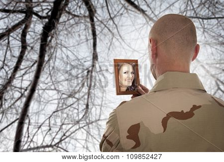 Soldier looks at the picture of the bride