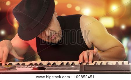 Man in the hat playing on a synthesizer