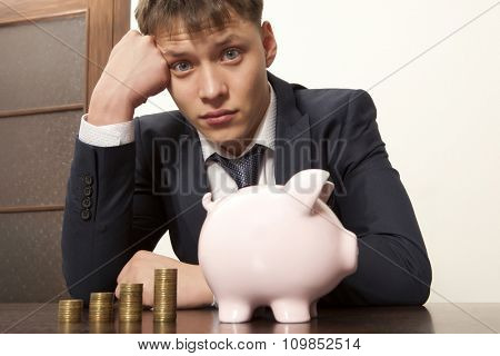 Businessman with pink piggy bank and coin