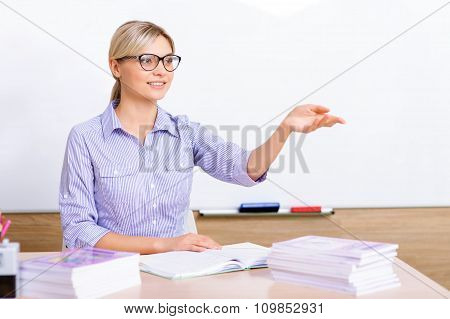 Teacher sitting at the desk and gesturing to pupils.